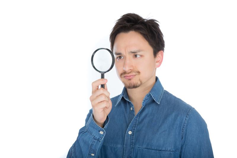 虫眼鏡で見ている男性